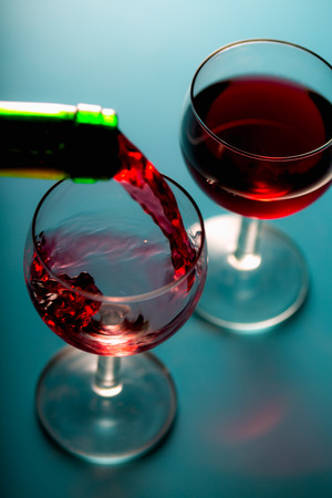 jet stream: Pouring wine into the glasses, blue background