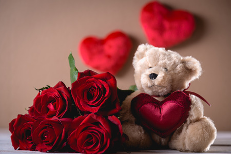 Valentines teddy bear with roses on bright background on wooden table Stock Photo