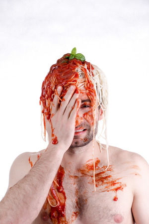 silly face: Funny man with spaghetti on head, white background Stock Photo