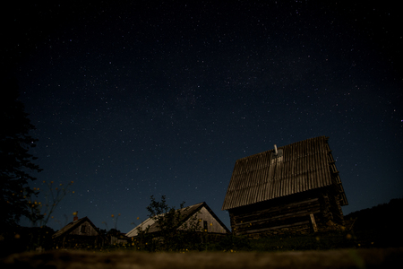 Night sky is full of stars, rural landscape with wooden village Stock Photo