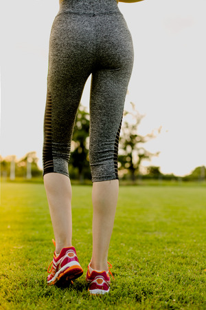 Young girl is stretching before running, training concept