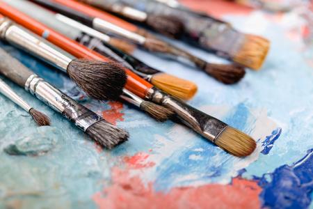 Pinceles viejos coloridos sobre fondo de pintura