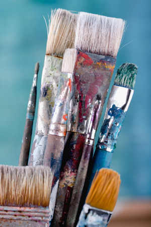 Paint brushes on light blue background, close up shot Imagens