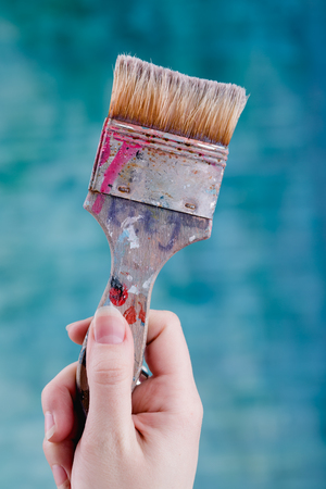 Paint brush in hand, close up shot of painting