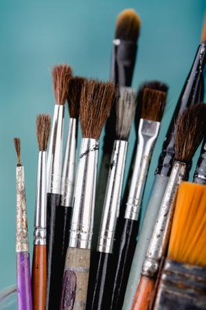 Paint brushes on light blue background, close up shot 免版税图像