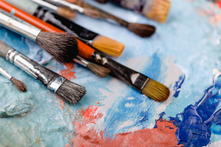 Colorful old brushes on painting background