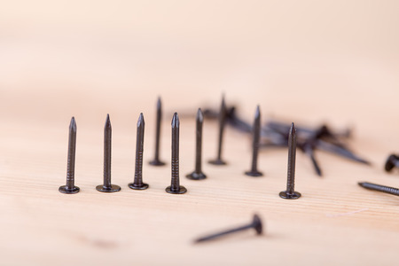 Nails on wooden table, tools and construction concept