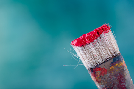 Brush with red paint on the top