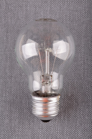Electric bulb on gray background, close up shot
