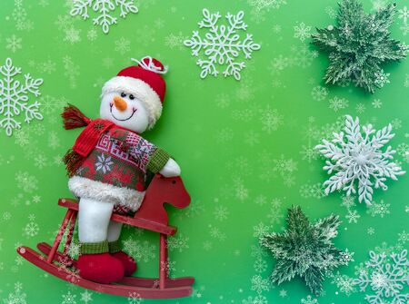 Snowman figurine on green Christmas background