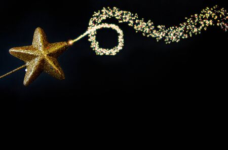 Christmas golden star magiс wand with fairy blowing dusty glitter curved line, isolated closeup on black background, template