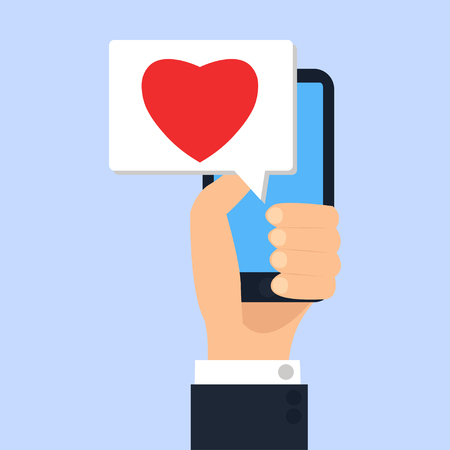 Hand holding smartphone with heart in message on screen, like button. Mobile media device