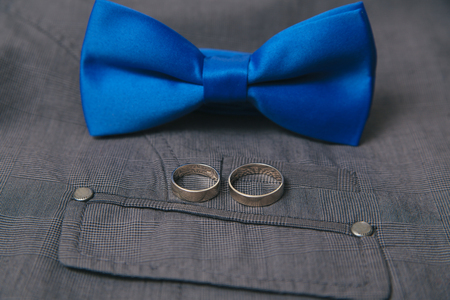 Blue bow tie with wedding rings on textile suit background