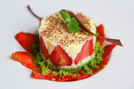 layered dessert with strawberries, biscuit cake and cream cheese on a dark wood background