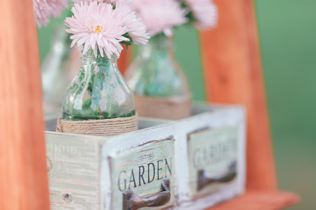 Rustic wedding photo zone. Hand made wedding decorations includes Photo Booth, wooden barrels and boxes, lanterns, suitcases and white flowers 스톡 콘텐츠