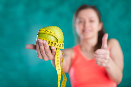 Diet. Healthy happy woman with apple and tape measure for diet and weight loss concept - isolated on the turquoise background. Sweets are unhealthy. Junk Food. Dieting, Healthy Eating.