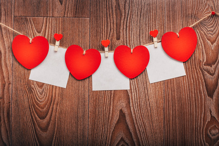 Love Valentines hearts and card natural cord and red clips hanging on rustic driftwood texture background, copy space Stock Photo
