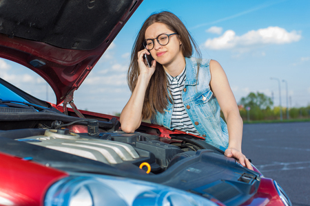 Girl near a broken car on the road.