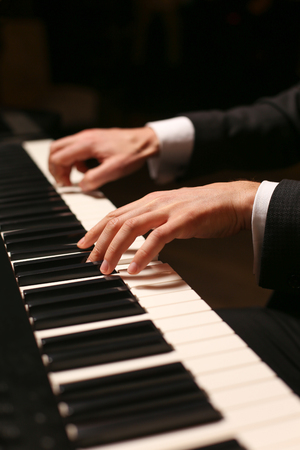 Closeup of hands playing piano. Фото со стока