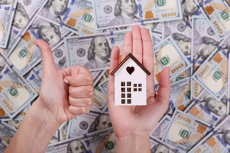 House model on hand with American dollar one hundred bills background.
