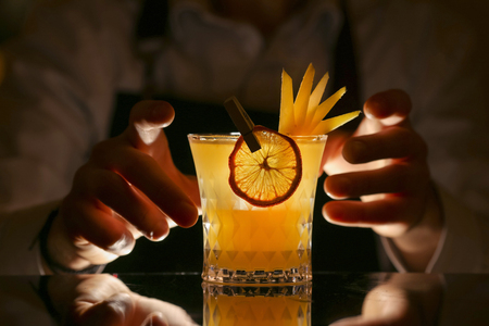 Fresh alcohol Penicillin cocktail with orange slice and ice cubes. Barmen is making Penicillin cocktail