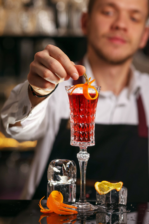 Kir Royal cocktail with orange slice and ice cubes.