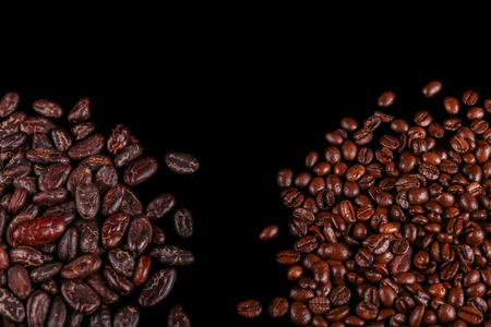 Roasted beans. Cocoa beans and coffee beans isolated on black background. Standard-Bild