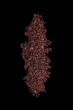 crushed cocoa beans on black background Standard-Bild