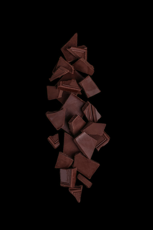 Pile chopped, milled chocolate isolated on black background
