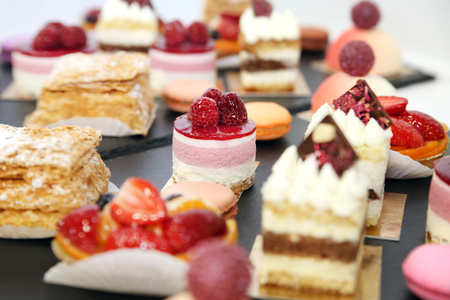 Assorted fruit cakes for holiday. Desserts with fruits, mousse, biscuits