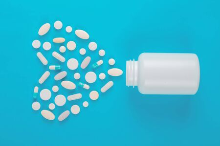 Assorted pharmaceutical medicine pills, tablets and bottle on blue background. Copy space for text
