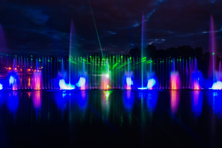 Night magic show of fountains on the central waterfront Roshen Ukrainian city of Vinnitsa Stock Photo