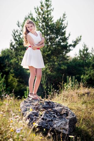 Summer photo smiling girl in a white dress on a background of green trees