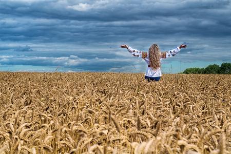 Achter mening van blonde incognito meisje met lang haar die zich onder het tarwegebied bevinden, wapens tot hemel. Het dragen van Oekraïense nationale reeks en ethnick overhemd en jeans. Panoramisch zicht op idillyc landschap.