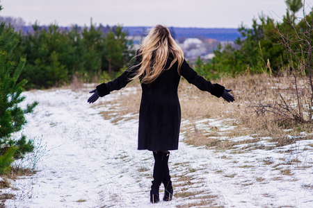 going green: A beautiful blonde girl going green in winter park with raising hands look back Stock Photo