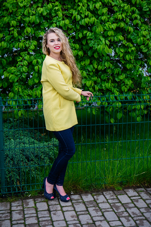 Attractive blonde in yellow coat emotionally posing at park