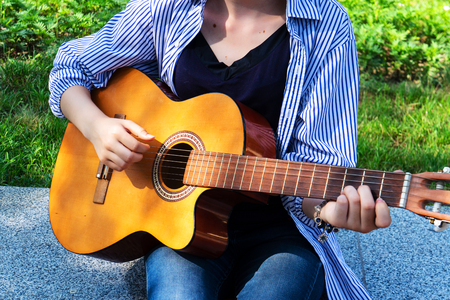 The girl plays the guitar chords on the guitar. Stockfoto