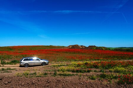 The car is on a dirt road. Field of flowers of red poppy. copy space.