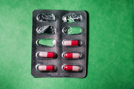 Pack of white red pills on a green background.