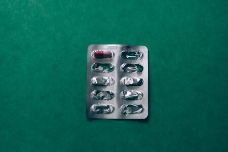 Pack of pills on green background. One tablet in the pack.