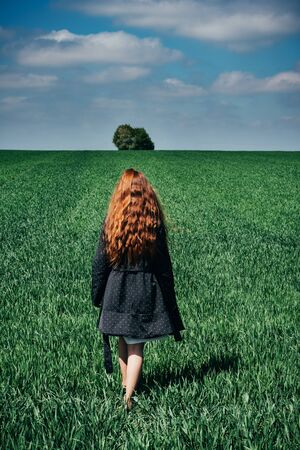 Back view of unrecognizable young woman in black coat walking on green grass on cloudy day in meadow. Redhead girl going to the lonely tree by the green field. Minimalist concept. Wheat field.