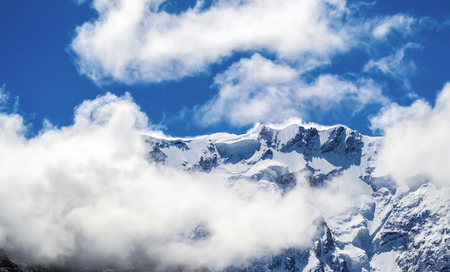 shrouded: Close view of snowy mountain ridge shrouded in clouds. Blue sky. Clear summit. North Caucasus.