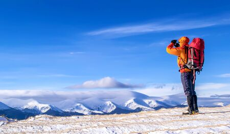 alpinist: Tourist with a backpack takes a picture of mountain range in the background of the blue sky. Carpathian, Ukraine. Stock Photo