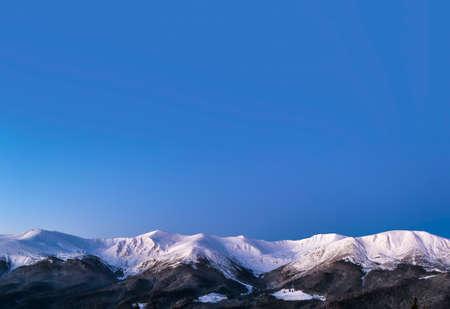 Winter morning view of snowy mountain ridge. Twilight before dawn.