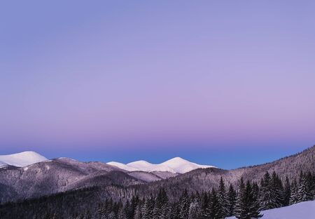 Winter morning view of snowy mountain peaks. Twilight before dawn.