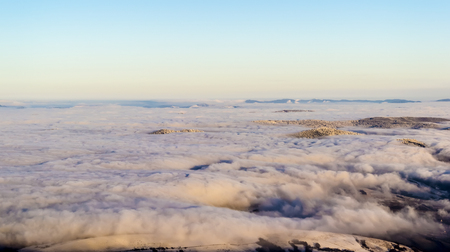 Scenic view, from the mountain top, of the clouds in the valleys. Zdjęcie Seryjne