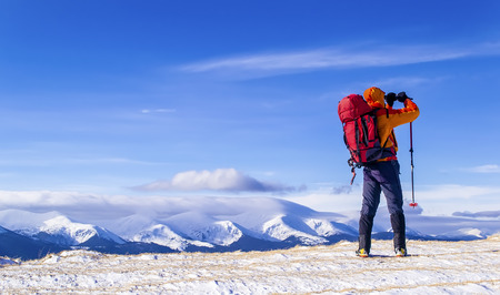 Hiker with a backpack takes a picture of mountain range in the background of the blue sky. Zdjęcie Seryjne