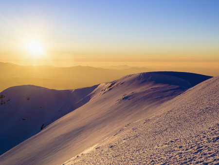 Scenic view of the sunset in the winter mountains. Direct sunlight. Sun rays. Zdjęcie Seryjne