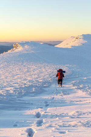 Tourist walking on a mountain ridge and left a trail in the snow. Evening.