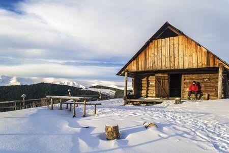Winter scene of mountain shepherd's yard. A man sits near old wooden house. The door is open.